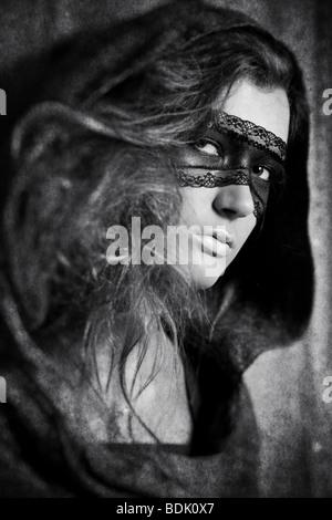 Giovane donna con maschera. Bianco e nero concetto con effetto invecchiato. Foto Stock
