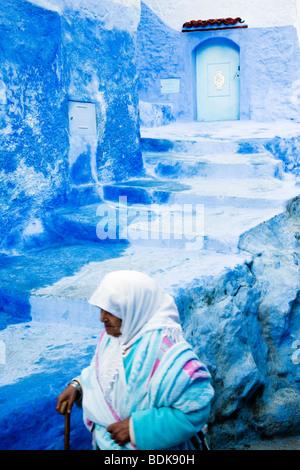 Chefchaouen, tradizionale blu-verniciato porte e pareti in città vecchia; vecchia donna in primo piano. Foto Stock