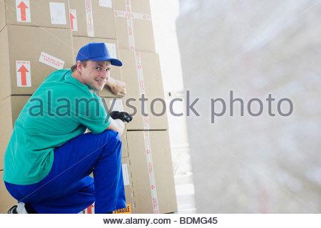 Uomo di consegna la nastratura di scatole di cartone in magazzino Foto Stock