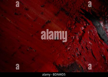 La vernice rossa sfaldatura di distanza in una fabbrica abbandonata. Foto Stock