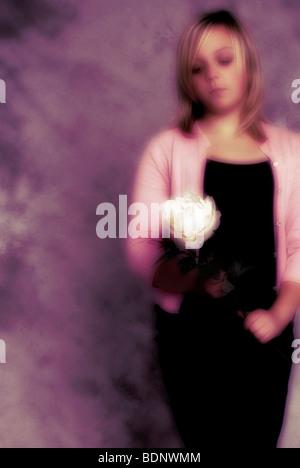 Una ragazza con una rosa bianca Foto Stock