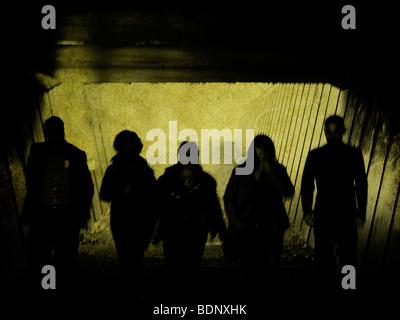 Stagliano figure camminando in un tunnel Foto Stock
