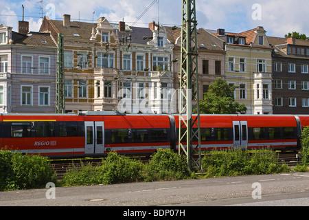 Treno regionale da Deutsche Bahn AG di fronte Gruenderzeit edifici, dal fondatore dell'epoca di periodo, nella città Foto Stock