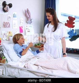 Bambino in ospedale - boy ricezione di ottenere ben carte in ospedale da un infermiere degli anni ottanta SerieCVS100023127 Foto Stock