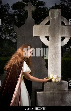 Giovane donna vittoriana mettere fiori su una tomba Foto Stock