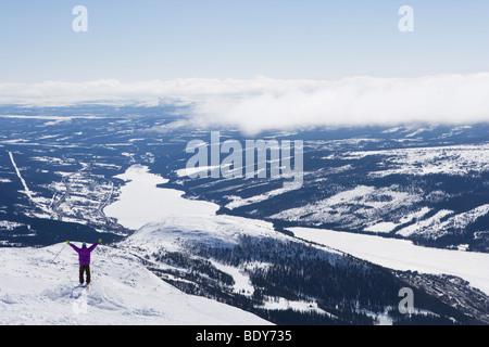 Uomo in piedi sul bordo scogliera a braccia alzate. Foto Stock