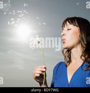 Donna soffiando tarassaco Foto Stock