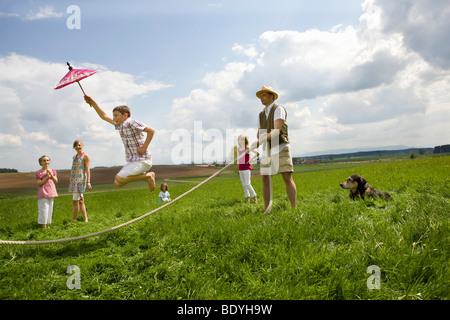 Le persone felici jump roping in campagna Foto Stock