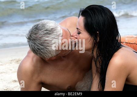 Felice Coppia di mezza età baciare sulla spiaggia, godendo le loro vacanze estive insieme.