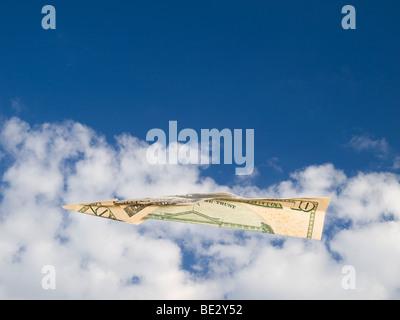 Un dieci dollari bill aereo volare sopra le nuvole su un cielo blu. Foto Stock