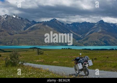 Moto Enduro su una strada di ghiaia al glaciale Lago Pukaki, con una vista sulle montagne del Ben Ohau gamma, Isola del Sud Foto Stock