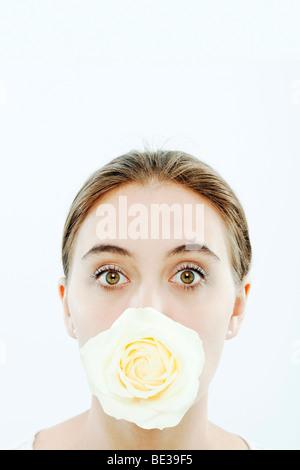 Ritratto di giovane donna con una rosa in bocca Foto Stock