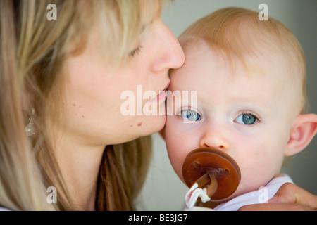 Un one-anno-vecchia ragazza sul braccio di sua madre Foto Stock