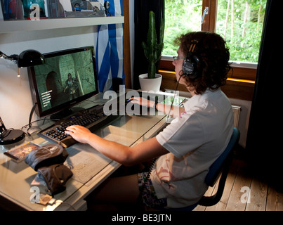 Un ragazzo, circa 15, la riproduzione di un gioco violento sul computer nella sua stanza, Germania, Europa Foto Stock