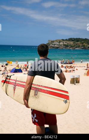 Un surfista si affaccia sulla spiaggia Bondi. Sydney, Nuovo Galles del Sud, Australia
