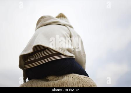 Bambino seduto su dei genitori di spalle, vista posteriore Foto Stock