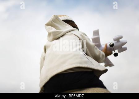 Ragazzo seduto su dei genitori di spalle, tenendo aeroplano giocattolo, vista posteriore Foto Stock