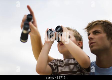 Padre e Figlio con il binocolo, uomo rivolto verso il cielo Foto Stock