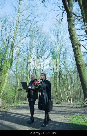 Due imprenditrici camminare insieme lungo il sentiero forestale uno utilizzando laptop, sia che trasportano fiori Foto Stock