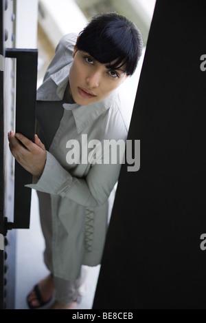 La donna porta di apertura, guardando la telecamera, ad alto angolo di visione Foto Stock