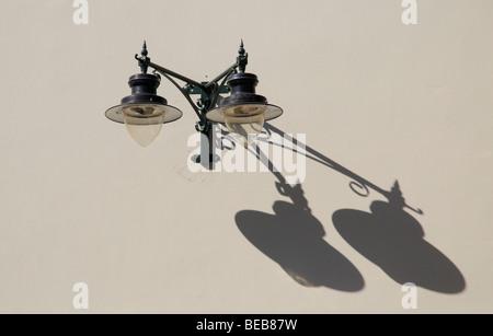 Illuminazione stradale due lampade elettriche gettare un'ombra su una luce parete colorata Foto Stock