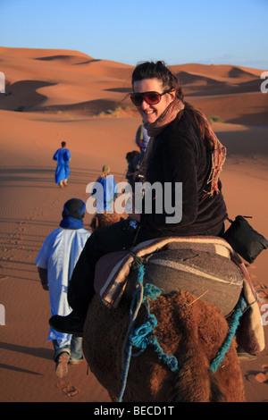Turista femminile su un cammello trek guidato da uomo blu attraversa Erg Chebbi dunesin di sabbia del deserto del Sahara vicino a Merzouga, Marocco Foto Stock