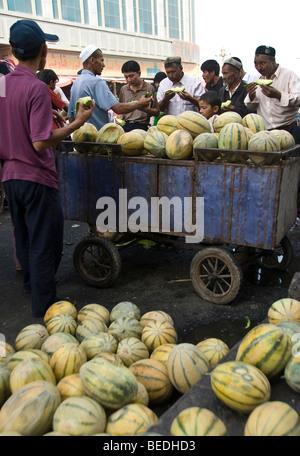 Persone che acquistano meloni freschi in un mercato di Kashgar, provincia dello Xinjiang, Cina. Foto Stock