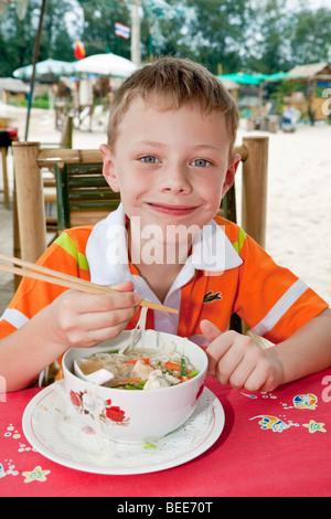 6-anno-vecchio ragazzo di mangiare la zuppa di noodle con bacchette Isola di Phuket Thailandia del sud sud-est asiatico