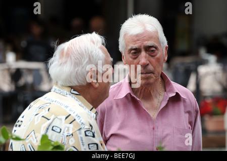 Due anziani vecchi pensionati uomini riuniti per la chat di mattina nella Piazza di Vigevano Lombardia Lombardia Foto Stock