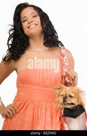 Ritratto di una giovane donna che porta un cane di Pomerania in un sacchetto e sorridente