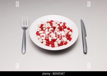 Concetto di cibo, piatto pieno di pillole Foto Stock
