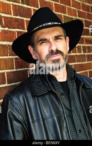 Uomo con la barba nel cappello da cowboy e giacca di pelle Foto Stock