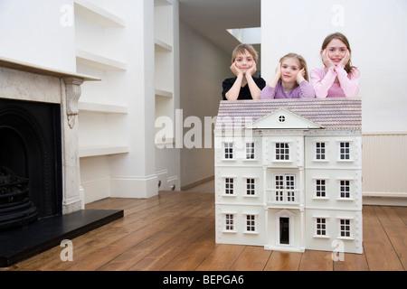 Tre bambini in appoggio su una dollhouse.
