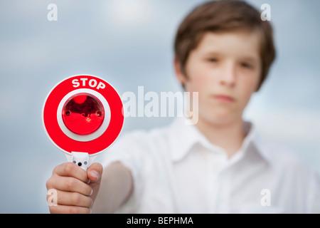 Ragazzo giovane azienda fino in segno di stop Foto Stock