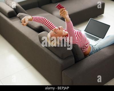Donna che mantiene la carta di credito con bracci sollevati. Angolo di Alta Vista, spazio di copia