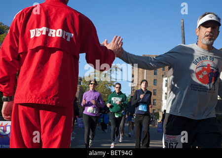 Detroit, Michigan - un membro di un club di traccia cheers su guide in Detroit Maratona Internazionale. Foto Stock