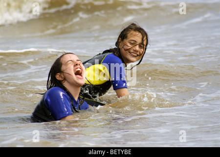 Due ragazze di nuoto in mare in mute avente un grande tempo a giocare con le onde Foto Stock