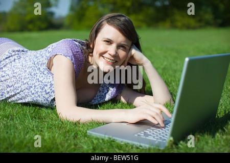Donna che utilizza computer portatile esterno Foto Stock