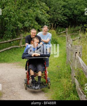 Ragazzo disabili essendo spinto lungo da amare i genitori. Foto Stock