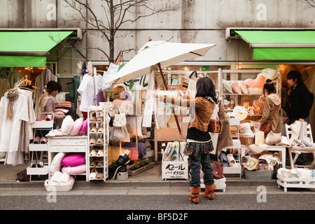 Una giovane donna si affaccia su alcuni articoli casalinghi in un negozio nella Shimokitazawa, Tokyo, Giappone Foto Stock