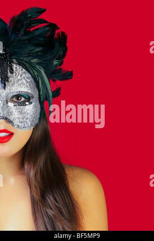 Bella bruna donna che indossa una maschera masqurade contro uno sfondo di colore rosso. Foto Stock