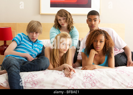Il gruppo di cinque amici adolescenti cercando annoiato In camera da letto Foto Stock