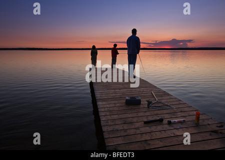 Un padre con i suoi due figli la pesca alla fine di un pontile sul Lake Audy al tramonto, Equitazione Mountain National Foto Stock