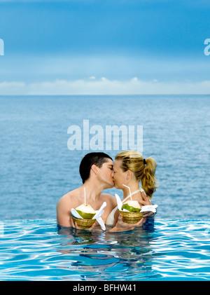 Bella coppia caucasica godersi la loro vacanza in una splendida piscina in riva al mare Foto Stock