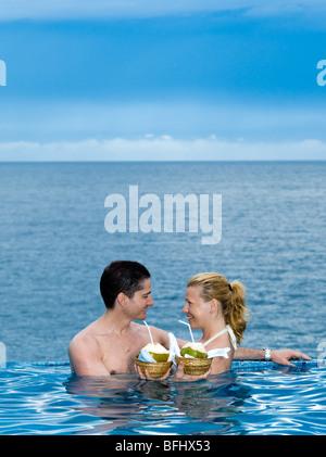 Bella coppia caucasica godersi la loro vacanza in una piscina in riva al mare a bere latte di cocco Foto Stock