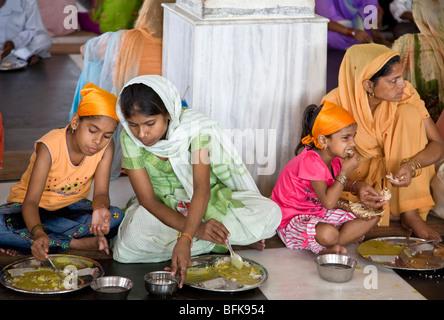Le donne indiane di mangiare un thali (tradizionale pasto indiano). Il tempio d'oro libera comunità sala da pranzo. Foto Stock