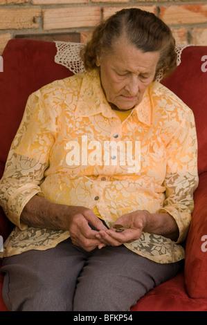 Anziana donna caucasica contare monete nelle sue mani Foto Stock