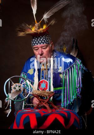 Native American Indian maschio in full regalia sporgendoti bruciando salvia ciotola con dream catcher in mano su Foto Stock