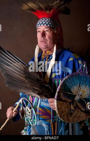 Native American Indian maschio in full regalia con dream catcher bird ala e protezione della gru su sfondo marrone Foto Stock