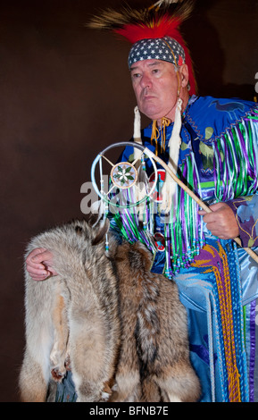 Native American Indian maschio con dream catcher e pellicce in piena regalia su sfondo marrone Foto Stock